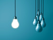 One hanging light bulb glowing and standing out from unlit bulbs on dark green pastel color background. 3D rendering.