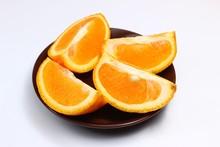 Cut Orange In A Plate On A Whi...