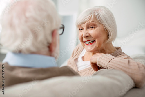 Cheerful smile. Portrait of a delighted elderly woman while looking at her husband