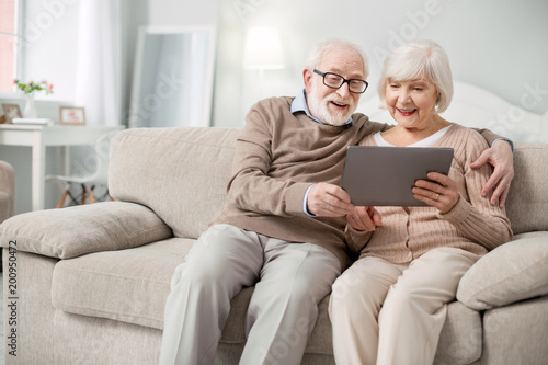 Obraz Modern device. Joyful aged people smiling while looking at the tablet screen - fototapety do salonu