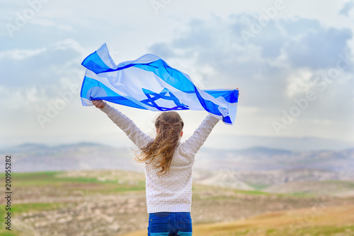 Little patriot jewish girl standing  and enjoying with the flag of Israel on blue sky background Canvas Print