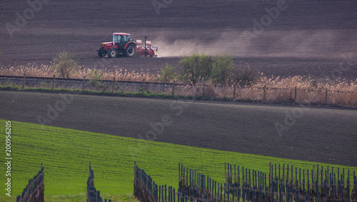 Fotobehang Aubergine tractor working on the field in spring