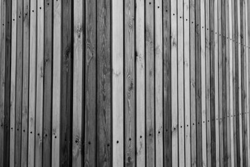 fragment of a wooden fence for a residential building. material from a log of a tree. urban geometry in black and white treatment