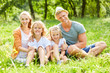 Glückliche Familie sitzt zusammen im Garten