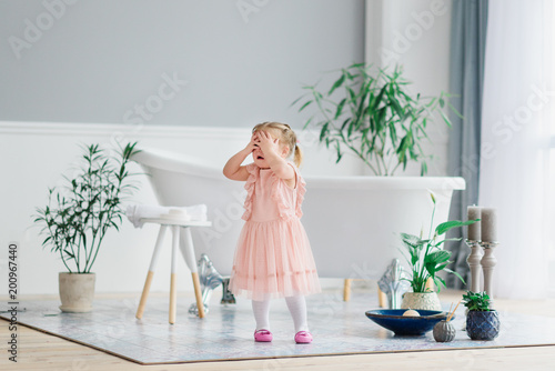 Fotografía  A little sweet girl stands in a large cozy light house near a white bathroom and closes her eyes with her hands with happiness