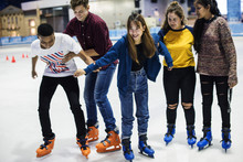 Group Of Teenage Friends Ice Skating On An Ice Rink