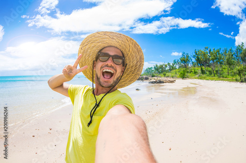 Handsome man having fun taking a selfie at the beach on holiday Wallpaper Mural