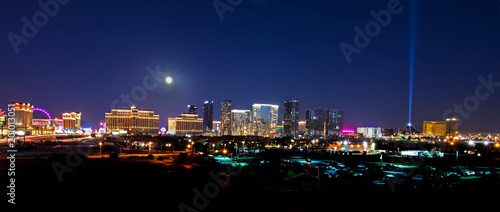 Photo  A view of the Las Vegas skyline with a full moon shining down.