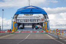 Ferry Boat Ship With Open Ramp And Empty Car Deck Ready To Board Cars And Passengers.