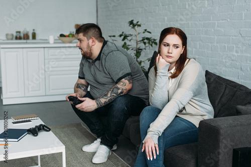 Fototapeta upset girlfriend sitting on sofa while boyfriend playing video game at home obraz na płótnie