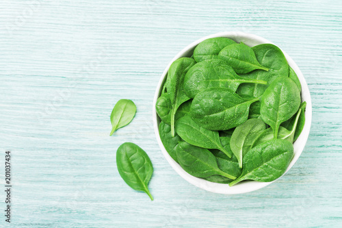 Green spinach leaves in bowl on table top view. Healthy food.