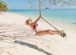 Happy woman in red bikini posing near the sea on the beach