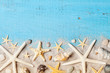 Composition from seashell, starfish and sand on blue table top view.