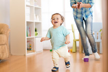 Baby Boy Running In The Living Room With His Mother