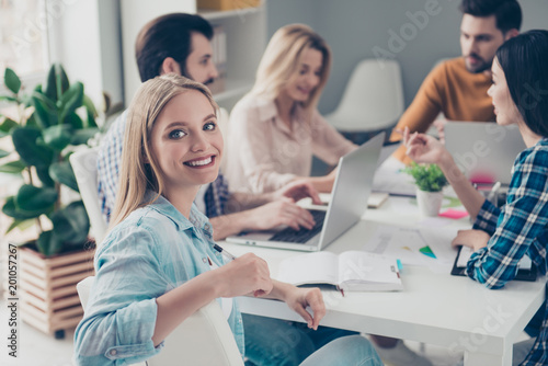 Tuinposter Klaar gerecht Beautiful, charming, stylish, pretty, cheerful, blonde woman in casual outfit sitting at the desktop with colleagues who discussing new project startup looking at camera enjoying working process