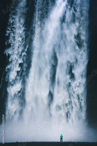 Tuinposter Fietsen Hiker at gigantic Skogafoss waterfall in Iceland