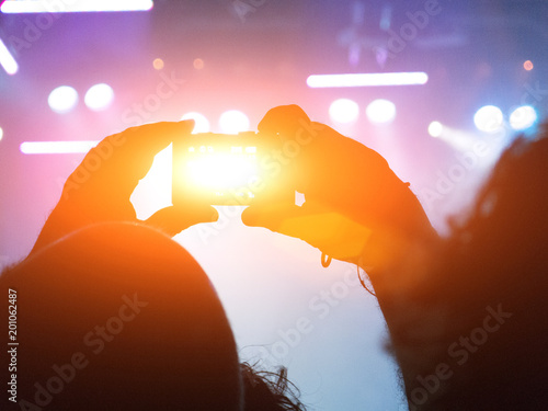 Photo Stands Sunset Close up on a handheld smart phone filming a live concert scene