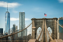 Brooklyn Bridge And One World Trade Center New York, Manhattan With US Flag And Airplane At Blue Sky. Panorama