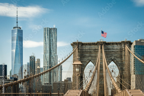 Cuadros en Lienzo Brooklyn Bridge and one world trade center New York, Manhattan with US flag and airplane at blue sky