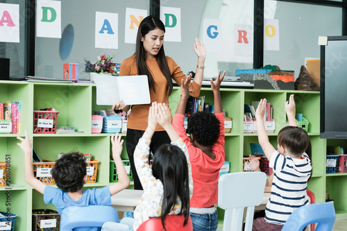 Young asian woman teacher teaching kids in kindergarten classroom, preschool edu Fototapeta