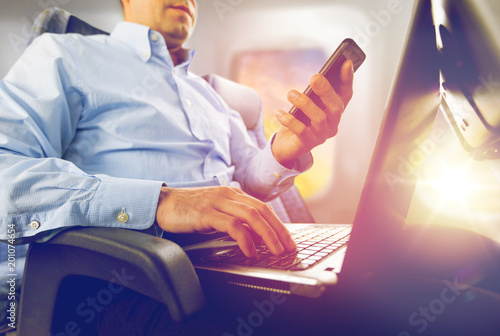 Poster Wintersporten transport, tourism and technology concept - close up of businessman with smartphone and laptop traveling by plane and working over porthole background
