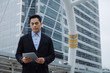 young handsome asian business man wearing modern black suit reading information about finance news with mobile tablet in building city background, network technology, internet, successful concept