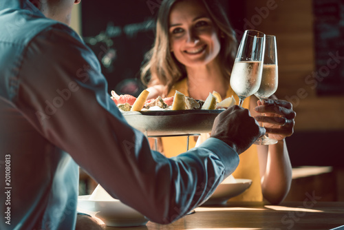 Happy young couple in love toasting with champagne during romantic dinner with seafood as oysters and crabs at the restaurant