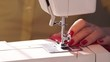 Woman sewing with modern sewing machine. A hand supporting a fleece cloth while sewing on a machine. red fabric. Woman's hands close up. Modern sewing machine. sewing with modern sewing machine.slow