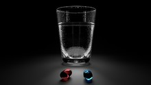 Two Red And Blue Drug Gel Capsules And A Glass Of Cold Water With Condensation Droplets Standing On A Table With Deep Black Background And Sharp Shadows