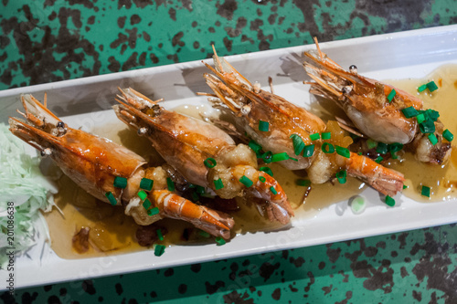 Grilled prawns sold at a street food market stall on a plate with sauce and herbs Poster