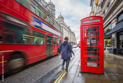 Poster Londres bus rouge London, England - Iconic blurred red double-decker bus on the move with traditional red telephone box and walking man in the center of London at daytime