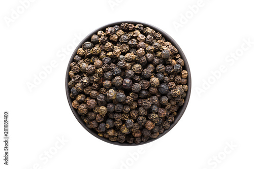 Black pepper grains in clay bowl isolated on white background. Seasoning or spice top view