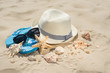 On the beach, a hat, sunglasses, sea shells and a star. On white sand
