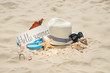 Hat on the beach, sunglasses, sea shells and a star and an inscription hi summer. On white sand