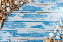 Sea Shells Frame On Vintage Blue Wooden Board. Summer Holiday Background.