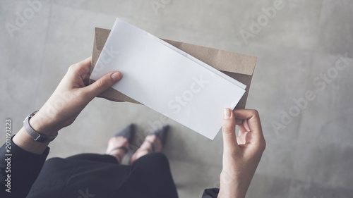 Stand up woman holding white folded a4 paper and brown envelope Fotobehang
