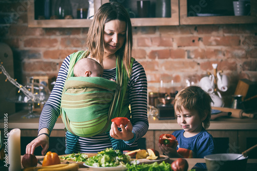 Fotografía  Happy young family, beautiful mother with two children, adorable preschool boy and baby in sling cooking together in a sunny kitchen