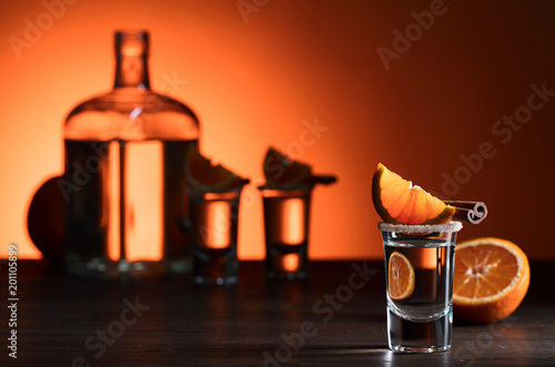 Staande foto Scandinavië Glasses of tequila with orange and cinnamon sticks on a wooden table.