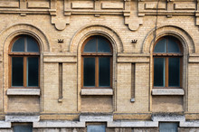 Three Vintage Arched Windows In A Wall Of Yellow Bricks. Green - The Colors Of Sea Wave Glass In A Maroon Dark Red Wooden Frame. The Concept Of Antique Vintage Architecture In Building Elements