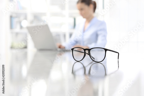 Cuadros en Lienzo eyeglasses leaning on desk and woman working on computer at office in background