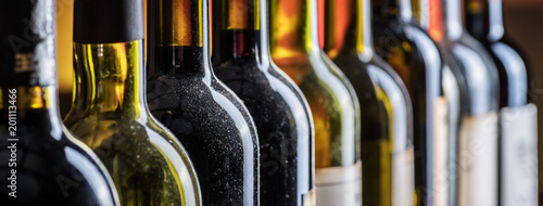 Photo  Line of wine bottles. Close-up.
