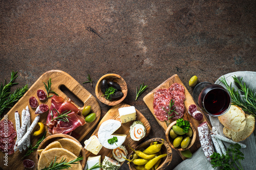 Photo Antipasto delicatessen - meat, cheese, olives and wine on stone
