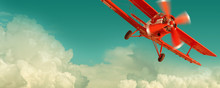 Red Biplane Flying In The Clou...