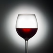 Large glass red wine shape of dark from grapes alcoholic beverage on luminous background advertising shot