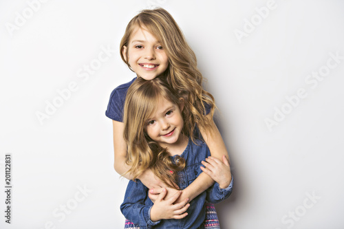 Fotografie, Obraz Joyful beautiful child with her sister close to a white wall
