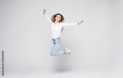 Obraz na płótnie Full length portrait of a cheerful woman jumping isolated on a white background