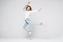 Full Length Portrait Of A Cheerful Woman Jumping Isolated On A White Background