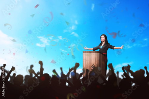Foto  Successful asian business woman giving a speech in front of the people