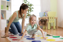 Cute Mother Playing Twister Wi...