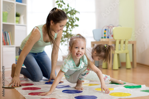 Photo  Cute mother playing twister with her daughters